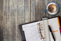 Anmerkungsbuchpapier mit Füllfederhalter, Gläsern, Machthaber und leerem Kaffee Lizenzfreies Stockbild