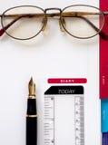 Anmerkungsbuchpapier mit Stift und Gläsern Stockfotografie
