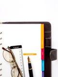 Anmerkungsbuchpapier mit Stift und Gläsern Stockfoto