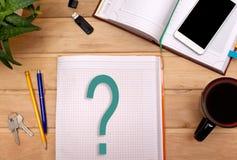 Anmerkungsfragen im Notizblock auf dem Schreibtisch eines Geschäftsmannes Lizenzfreie Stockbilder