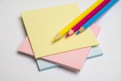 Anmerkungspapier und farbige Bleistifte Stockbild