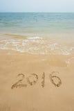 Année 2016 écrite en sable sur la plage Image stock