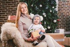 Année d'hiver de vacances de Noël de thème nouvelle Une jeune mère caucasienne élégante tient son fils dans des ses bras pendant  image libre de droits