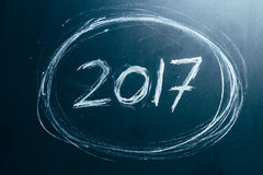 Année numéro 2017 écrit avec la craie blanche sur le tableau noir Photo stock