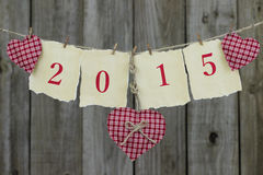 Année 2015 sur le papier antique avec les coeurs rouges accrochant sur la corde à linge par la barrière en bois Images libres de droits
