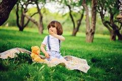 3 années élégantes belles d'enfant en bas âge de garçon d'enfant avec le visage drôle dans des bretelles appréciant des bonbons s Photo libre de droits