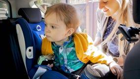 2 années adorables de bébé garçon dans le siège de sécurité de voiture Photos libres de droits