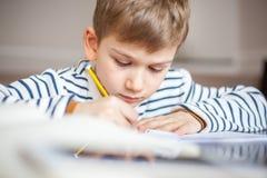 7 années adorables de garçon s'asseyant au bureau avec le livre et l'inscription Photo libre de droits