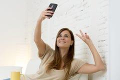 30 années attrayantes de femme jouant sur le divan à la maison de sofa prenant le portrait de selfie avec le téléphone portable Photo stock