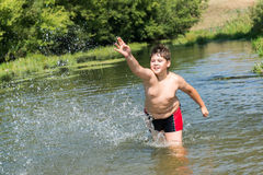 10 années complètes de bain de garçon en rivière Photo stock