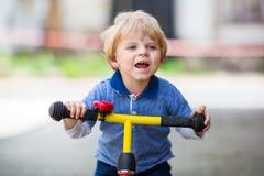 2 années d'équitation d'enfant en bas âge sur son premier vélo Images libres de droits