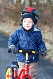 2 années d'équitation d'enfant en bas âge sur son premier vélo Photo stock
