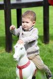 2 années de bébé garçon jouant avec le cheval Photos libres de droits