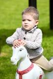 2 années de bébé garçon jouant avec le cheval Photo libre de droits