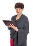65 années de femme recherchant dans l'Internet, Londres Images stock