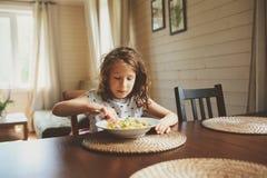 8 années de fille heureuse d'enfant mangeant des pâtes à la maison Photos stock