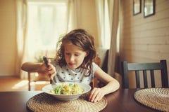 8 années de fille heureuse d'enfant mangeant des pâtes à la maison pour le déjeuner Photographie stock libre de droits