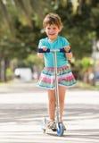 4 années de fille restant avec le scooter Image libre de droits