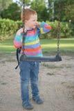 5 années de garçon heureux de roux manipulant son sac à dos à côté d'une oscillation et d'une rêverie images libres de droits