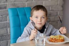 7 années de garçon mangeant du lasagne dans la salle à manger Photographie stock libre de droits