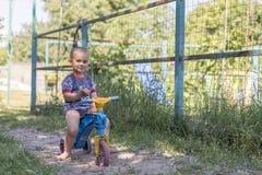 2 années de jeu de garçon avec la bicyclette, vélo d'équilibre garçon 2 ans montant une bicyclette par le village Photo stock