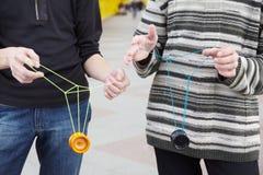 Années de l'adolescence avec des jouets de yo-yo dans des mains. orientation sur des vêtements Photographie stock libre de droits