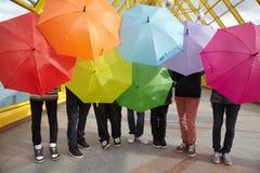 Années de l'adolescence avec les parapluies ouverts en passage supérieur piétonnier Photographie stock libre de droits