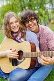 Années de l'adolescence ayant l'amusement avec la guitare dans le stationnement Image libre de droits