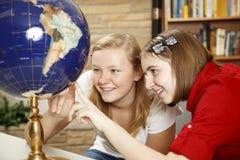 Années de l'adolescence de bibliothèque regardant le globe Images libres de droits