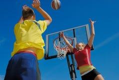Années de l'adolescence jouant au basket-ball Photographie stock