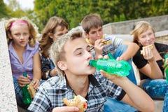 Années de l'adolescence mangeant des sandwichs Photographie stock