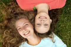 Années de l'adolescence se situant dans une herbe Photo stock