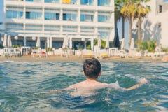 13 années de natation et relaxation de garçon dans les vagues de mer Concept des vacances d'été de famille photos stock
