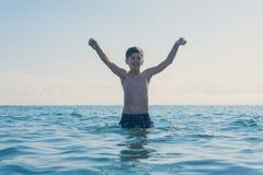 13 années de natation et relaxation de garçon dans les vagues de mer Concept des vacances d'été de famille photo libre de droits