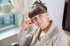 65 années de portrait de femme belle dans l'environnement domestique Image stock