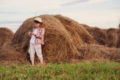 7 années heureuses de fille d'enfant dans la chemise et le chapeau de plaid de style campagnard détendant sur le champ d'été avec Image stock