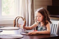 8 années heureuses de fille d'enfant prenant le petit déjeuner dans la cuisine de pays, lait boisson et mangeant du pain grillé Image stock