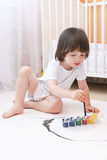 2 années mignonnes de garçon avec des peintures de brosse et de gouache à la maison Photo libre de droits