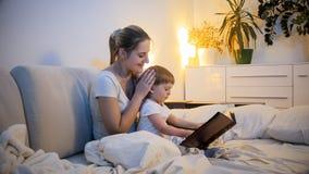 2 années mignonnes de garçon d'enfant en bas âge lisant le grand livre d'histoire dans le lit la nuit Photo libre de droits