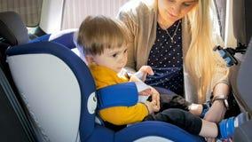 2 années mignonnes de garçon d'enfant en bas âge s'asseyant dans le siège de sécurité de voiture Photographie stock
