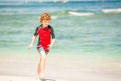 7 années mignonnes de garçon dans le costume de natation rushwest rouge Photo stock
