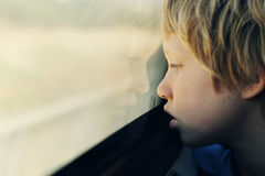 7 années mignonnes de garçon regardant par la fenêtre Photo stock