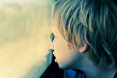 7 années mignonnes de garçon regardant par la fenêtre Photos libres de droits