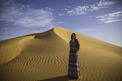 Anna που θέτει στο μέτωπο έναν μεγάλο αμμόλοφο άμμου Στοκ εικόνα με δικαίωμα ελεύθερης χρήσης