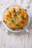 Anna potatoes with butter on a plate. Vertical  top view Stock Image