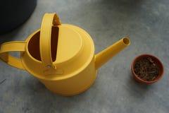 Annaffiatoio giallo con il vaso asciutto di tonnellata Fotografia Stock