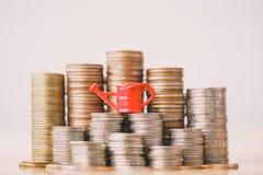 Annaffiatoio rosso sulla pila dei soldi fotografia stock libera da diritti