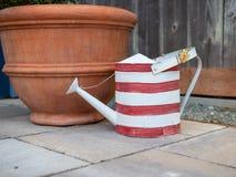 Annaffiatoio spogliato rosso e bianco che colloca accanto al grande vaso di fiore su calcestruzzo dietro il recinto fotografia stock libera da diritti