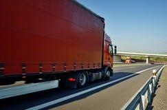 Annalkande röda lastbilar på den tomma huvudvägen i bygden Royaltyfria Foton