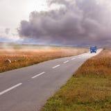 Annalkande storm och lastbil på vägen Arkivbilder